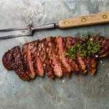 Sliced grilled beef barbecue Striploin steak with chimichurri sauce and meat fork on gray stone slate background