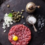 Beef Steak Tartare with capers and fresh onions on dark textured stone background