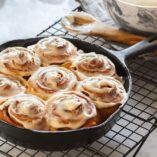 Homemade cinnamon rolls or buns baked in a cast iron skillet and smothered in cream cheese icing. The skillet is cooling atop a black wire cooling rack on a white and gray marble countertop. A bowl of icing and a wooden spoon are in the background.